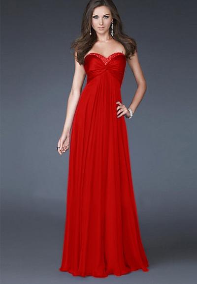 Modelo usa vestido tomara que caia vermelho, longo vibrante.
