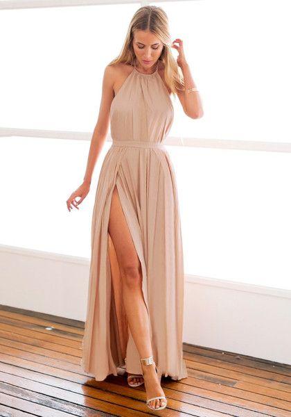 Modelo usa vestido nude frente única com fenda.