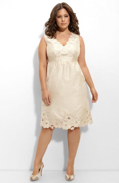 Modelo usa vestido na cor creme, decote v, curto plus size com sapato nude.