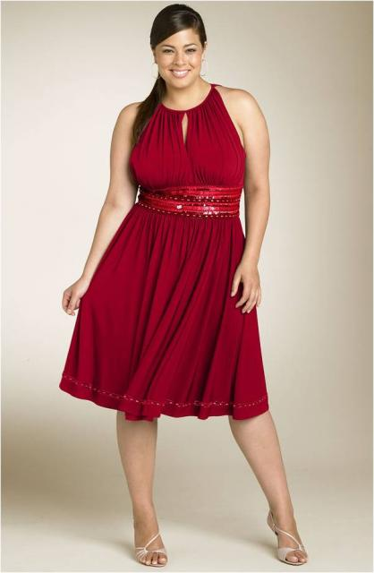 Modelo usa vestido curto, plus size na cor vermelho sem decote.