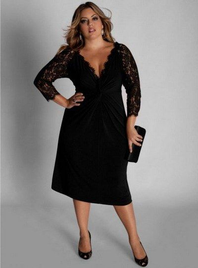 Modelo usa vestido preto plus size com decote V e sapato preto.