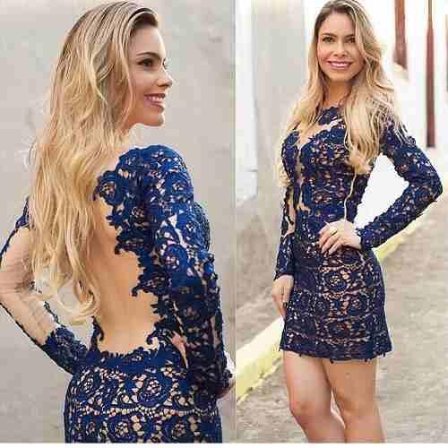 Modelo usa vestido azul escuro com decote nas costas , manga longa todo de renda.