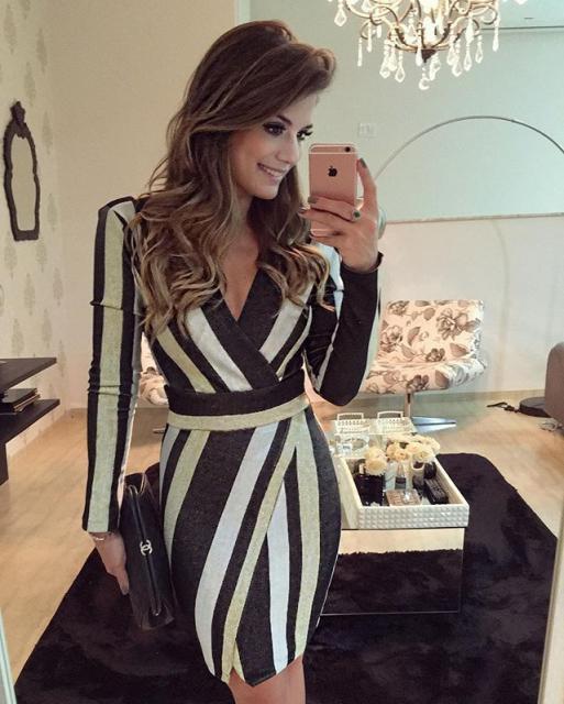 Modelo usa vestido listrado em preto e branco, modelo curto combinado com clutch preta.