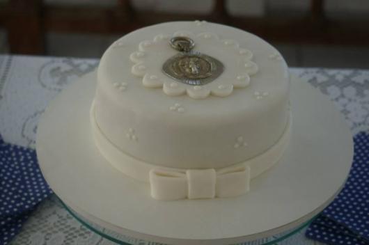 Bolo de batizado feminino coberto com pasta americana branca e detalhe de medalinha