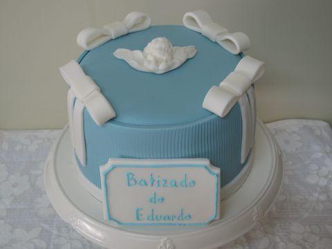bolo de batizado azul com laços brancos e um anjinho encima