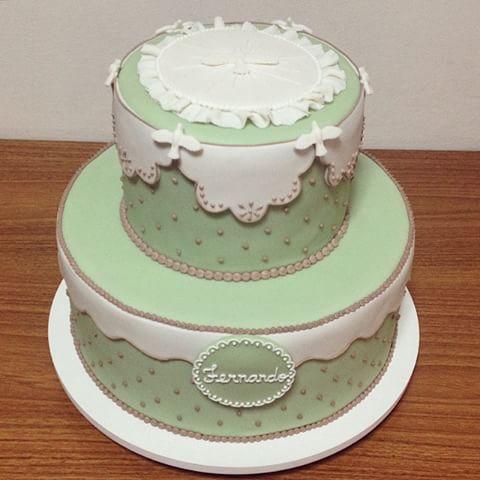 bolo de batizado azul com detalhes brancos e dourados, e pombinhas brancas