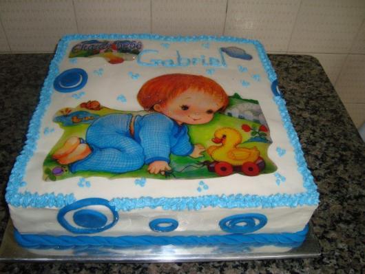 bolo de batizado azul e branco com papel de arroz de uma criança brincando