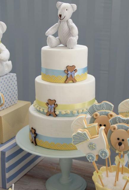bolo de três andares branco com fitas e ursinhos encima e ao lado