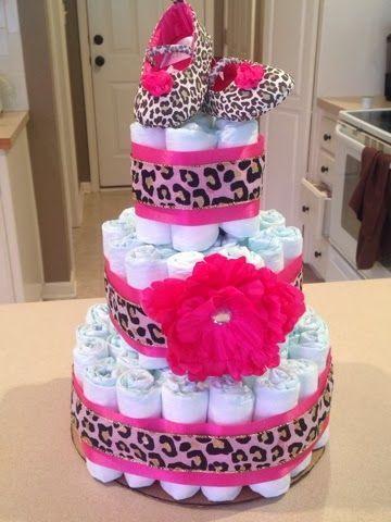 bolo fake feminino temático de oncinha, com uma flor, fitas estampadas de oncinha, e sapatinhos de oncinha