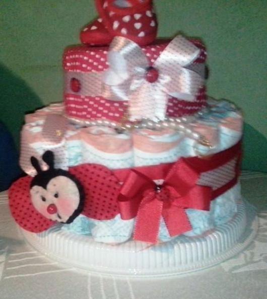 bolo fake feminino temático de joaninha, com estampa vermelha de bolinhas e laços