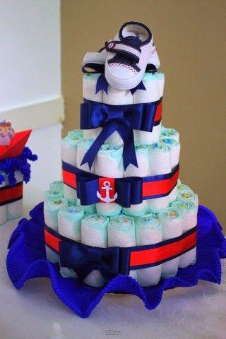 bolo fake masculino com laços azul, fita azul e vermelha, símbolo de marinheiro e um par de sapatinhos de bebê encima