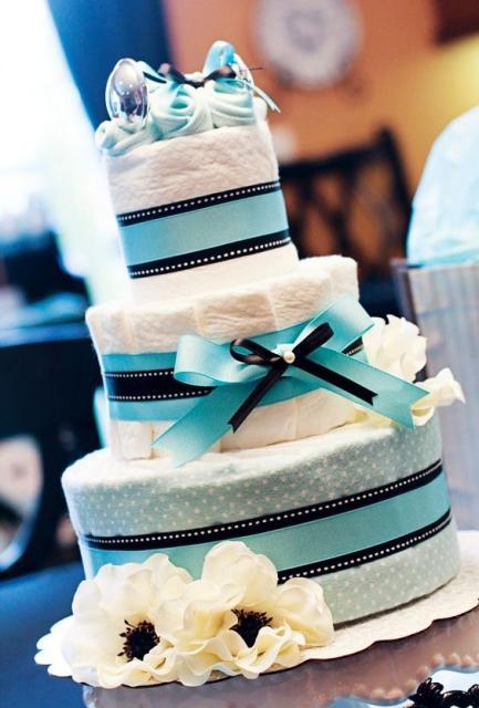 bolo fake masculino com laço azul claro e fitas da mesma cor, conta com um par de sapatinhos de bebê encima