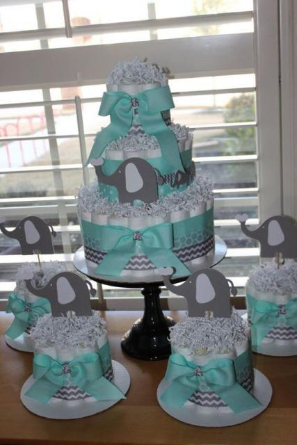 bolo fake masculino com laços da cor azul clara e desenhos de elefante cinza