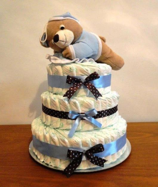 bolo fake masculino com lacinhos estampados com bolinhas azuis e um só azul, conta com um ursinho de pelúcia encima