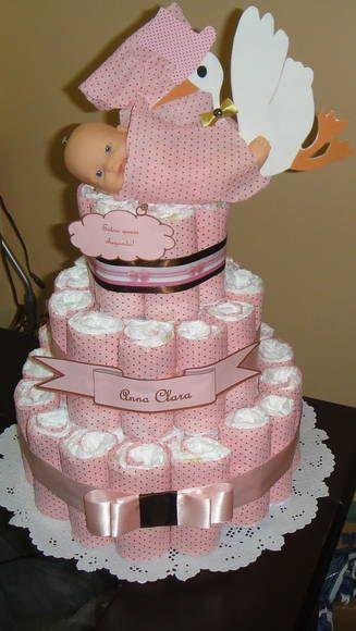 bolo fake feminino com estampa rosa de bolinhas, laço da mesma cor e uma boneca com uma cegonha encima