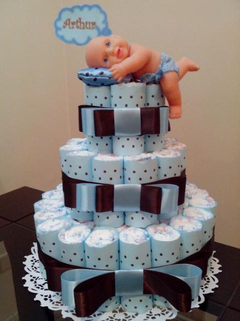 bolo fake masculino com laços maiores, estampa azul de bolinhas e uma boneca deitada em um travesseiro encima
