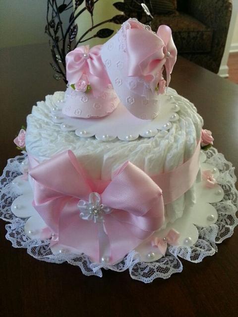 bolo fake feminino branco com um grande laço rosa e sapatinhos de bebê rosa encima