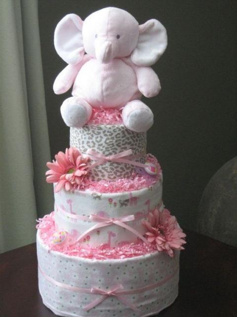 bolo fake feminino com flores da cor rosa, lacinhos rosa e um elefante rosa encima