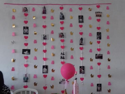 cortina de corações intercalados com fotos do casal e a mamãe grávida. Também conta com desenhos de animaizinhos