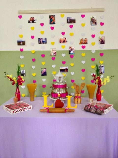 cortina de corações rosa e amarelo ao fundo da mesa de doces