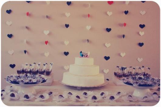 cortina de corações vermelho, preto e branco ao fundo da mesa de doces e bolo com duas corujinhas