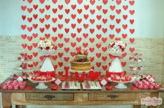 cortina de coração vermelho e branco ao fundo da mesa de doces