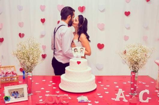 cortina de corações vermelho, rosa e branco com o casal se beijando na frente