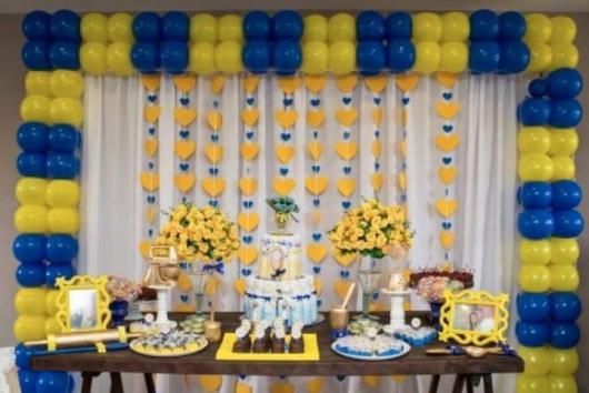 cortina de corações amarelo e azul ao fundo da mesa de doces