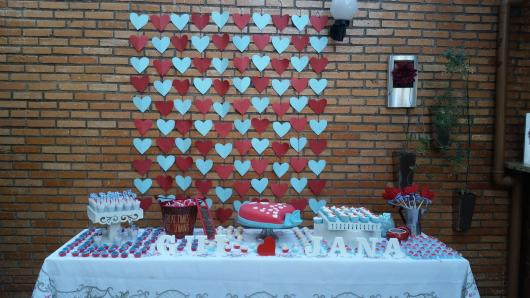 cortina de corações vermelho e azul ao fundo da mesa de doces