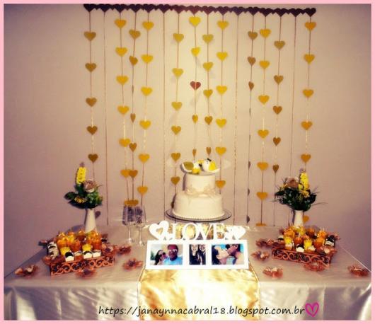 cortina de coração dourado ao fundo da mesa de doces, que conta com fotos do casal