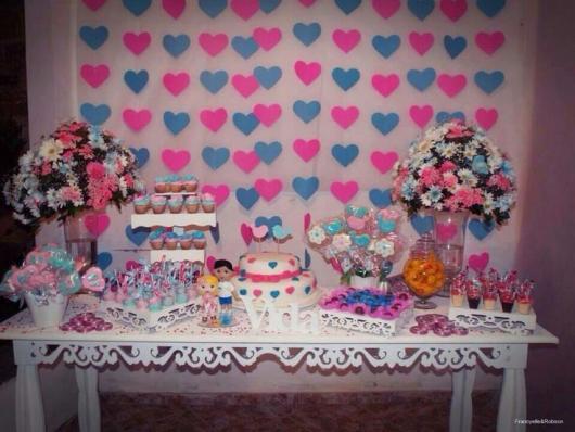 cortina de corações azul e rosa ao fundo da mesa de doces