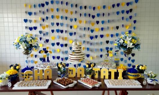 cortina de corações azul e amarelo ao fundo da mesa de doces