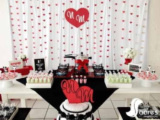 cortina de coração vermelho ao fundo da mesa de doces