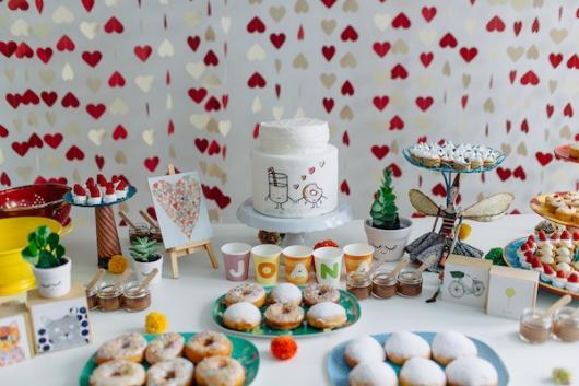 cortina de corações ao fundo de mesa com vários desenhos fofos e mesa de doces