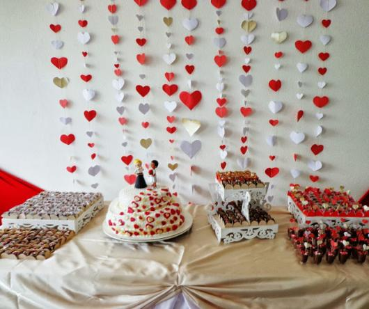 cortina de corações vermelho e branco ao fundo da mesa de doces