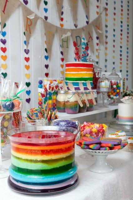 cortina de corações colorida e mesa de doces com bolo das mesmas cores
