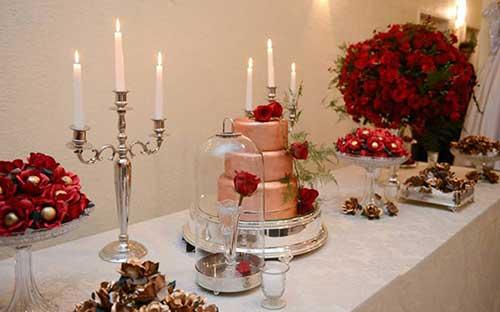 mesa de bolo dourado com flores vermelhas