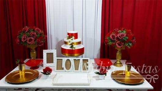 mesa de bolo com fitas vermelhas e douradas