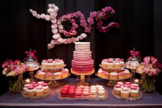 """mesa de bolo com tons de rosa e flores formando a palavra """"Amor"""" ao fundo"""