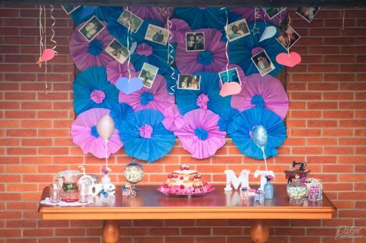mesa de bolo com detalhes ao fundo rosa e azul com fotos