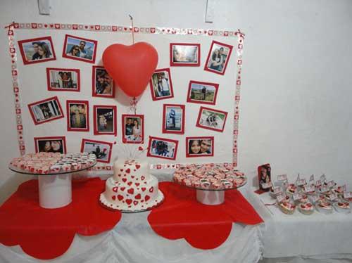 mesa de bolo vermelha e branca com fotos ao fundo