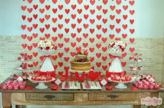mesa de bolo com cortina de corações ao fundo