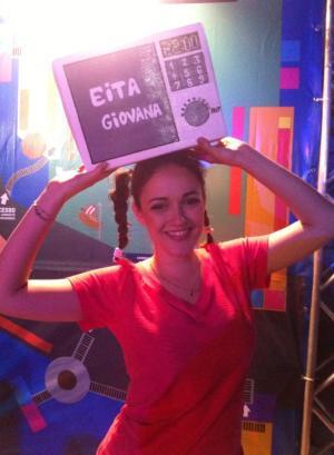 garota segurando plaquinha escrita Eita Giovana