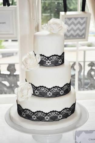 Bolo branco com detalhes com aparência de renda preta e flores