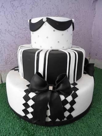 bolo com dois andares branco com detalhes em preto, e um andar preto com detalhes em branco. Tem um laço também