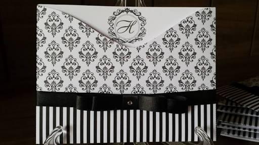 convite branco com detalhes em preto, inclusive laço