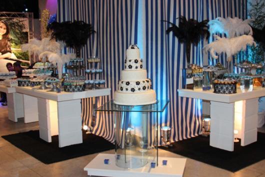 mesas de doces com plumas encima e bolo de flores ao meio