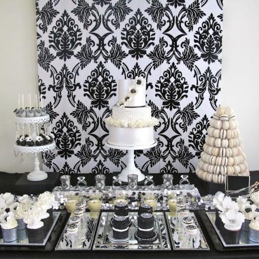 mesa de doces com desenhos em arabesco ao fundo