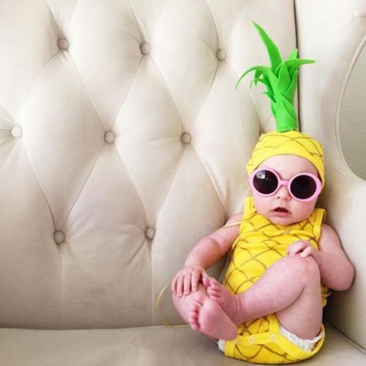 Bebê vestido de abacaxi, com óculos de sol.