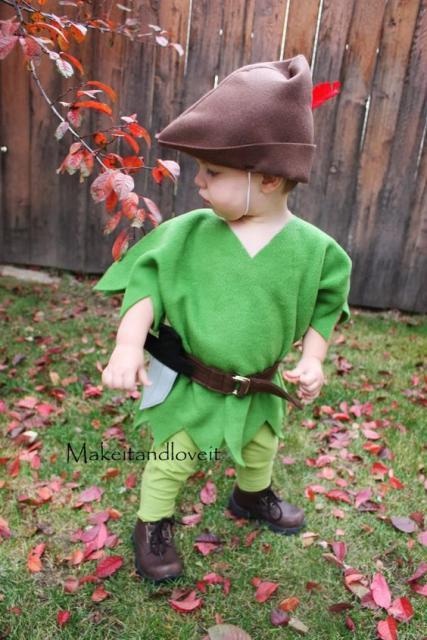 Menino vestido de Peter Pan, com roupa verde e touca marrom.